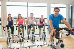 Stock Photo of Happy man teaches spinning class to four people
