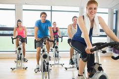 Stock Photo of Happy woman teaches spinning class to four people