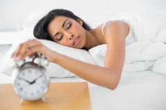 Lovely tired woman turning off the classic alarm clock - stock photo