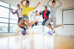 Stock Photo of Fit people jumping in bright exercise room