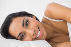 Gorgeous calm woman lying under the cover on her bed - stock photo