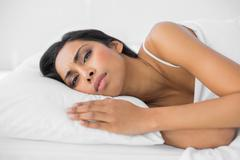 Young attractive woman lying on her bed wrinkling her brow Stock Photos