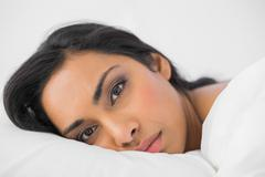 Attractive woman lying in her bed looking seriously at camera - stock photo