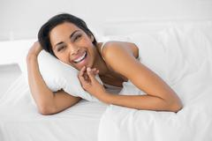 Content laughing woman lying under the cover on her bed - stock photo