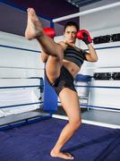 Stock Photo of Female boxer performing an air kick in the ring