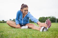Stock Photo of Sporty woman stretching her leg on grass