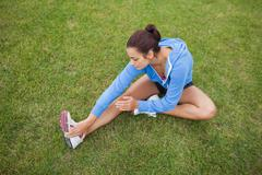 Sporty woman stretching her leg while sitting on the grass Stock Photos