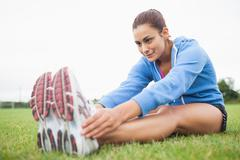 Stock Photo of Sporty woman stretching her legs while sitting on grass