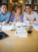 Adult students studying together in the library - stock photo