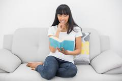 Calm dark haired woman reading a book sitting on couch - stock photo