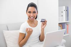 Beautiful successful woman home shopping with her notebook - stock photo