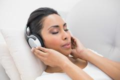 Enjoying natural woman listening to music lying on couch Stock Photos