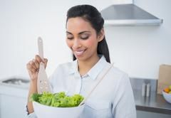 Stock Photo of Cute calm woman preparing salad standing in kitchen