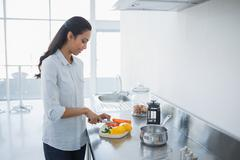 Content woman preparing salad standing in bright kitchen Stock Photos