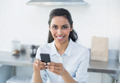 Natural smiling woman holding her smartphone looking at camera - stock photo
