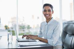 Cheerful smiling businesswoman working on her laptop - stock photo