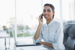 Young black haired businesswoman sitting at her desk Stock Photos