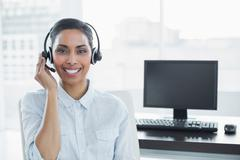 Cute smiling agent wearing headset looking at camera - stock photo
