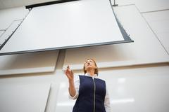 Elegant teacher with projection screen in the lecture hall - stock photo
