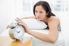 Stock Photo of Woman in bed extending hand to alarm clock