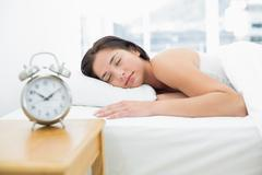 Sleeping woman with blurred alarm clock in foreground - stock photo