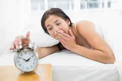 Woman yawning while extanding hand to alarm clock - stock photo