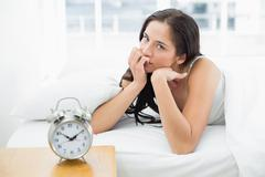 Woman in bed with alarm clock in foreground Stock Photos