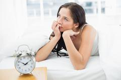 Woman in bed with alarm clock in foreground - stock photo