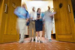 Group of blurred people walking through open doors - stock photo