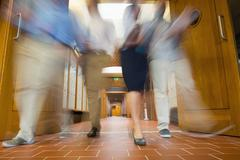 Stock Photo of Group of blurred people walking through open doors