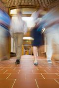 Blurred people walking through open doors - stock photo