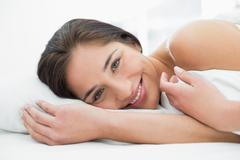 Close up of a pretty smiling woman resting in bed - stock photo