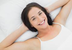 Pretty smiling young woman resting in bed - stock photo
