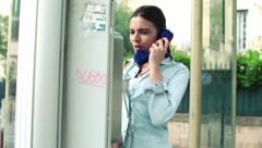 Worried woman try to make call in broken telephone booth HD - stock footage