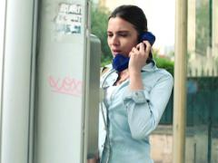 Worried woman try to make call in broken telephone booth NTSC Stock Footage