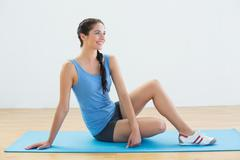 Stock Photo of Full length of a woman sitting on exercise mat
