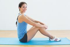 Portrait of a fit woman sitting upright on exercise mat Stock Photos