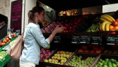Young woman smelling and buying fruit in greengrocer HD - stock footage