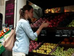 Young woman smelling and buying fruit in greengrocer NTSC Stock Footage