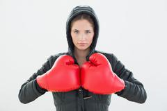 Serious young woman in red boxing gloves and black hood Stock Photos