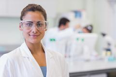 Female researcher with colleagues in background at lab - stock photo