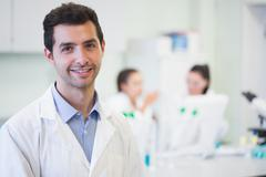 Smiling researcher with colleagues in background at lab - stock photo