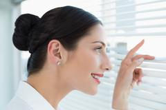 Smiling young business woman peeking through blinds at office - stock photo