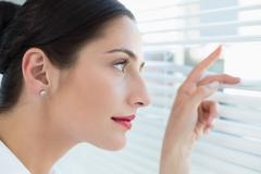 Young business woman peeking through blinds at office - stock photo