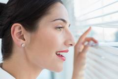 Smiling business woman peeking through blinds at office - stock photo