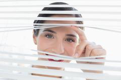Smiling young business woman peeking through blinds - stock photo