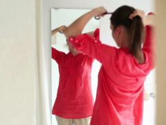 Young beautiful woman making ponytail in front of mirror NTSC Stock Footage