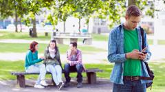 College boy text messaging with blurred students in park Stock Photos