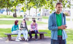 Stock Photo of College boy text messaging with blurred students in park