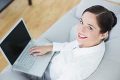 Stock Photo of Smiling well dressed young woman using laptop on sofa